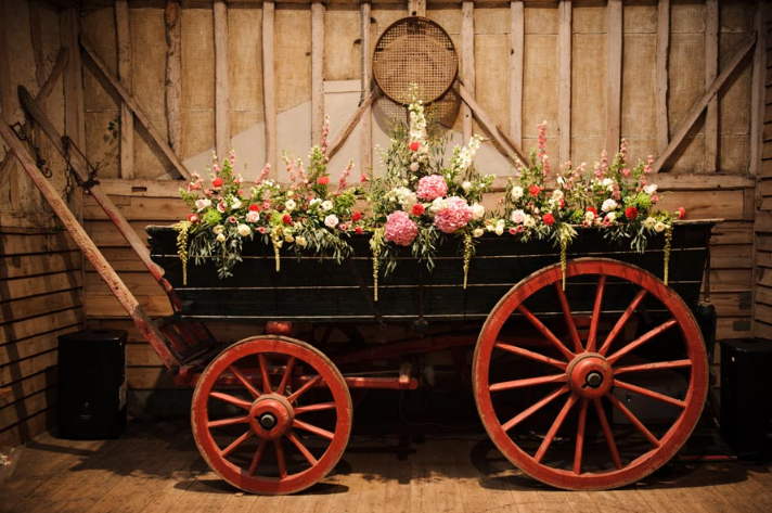Flowers filled a Wheelbarrow at Barn Wedding with a Country Chic Feel